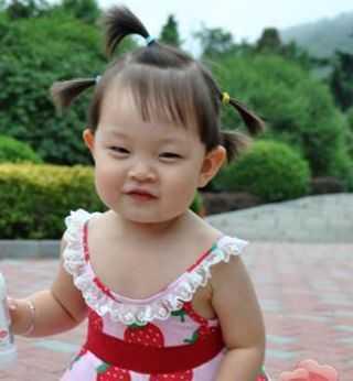 三岁大的小女孩梳理着稀疏的中发蘑菇头发型,在夏天妈妈将小女孩的图片